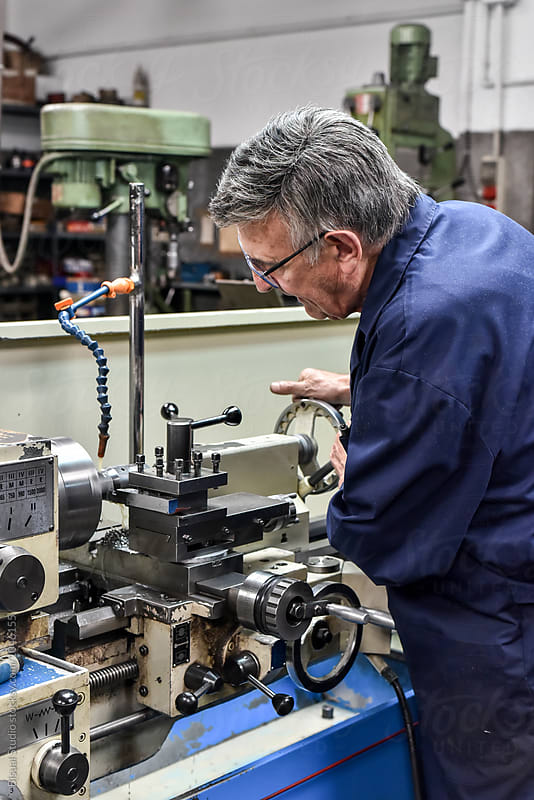 senior man using industrial lathe machine by Bisual Studio for Stocksy United