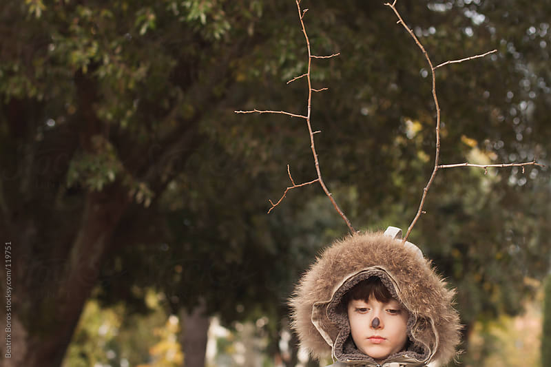 Portrait of a sad boy wearing deer antlers. by Beatrix Boros for Stocksy United