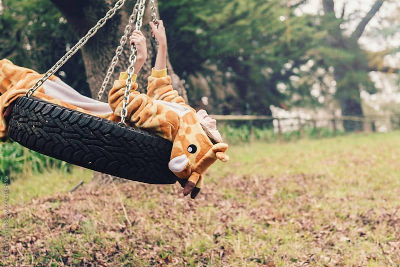 tween girl on an outdoor swing, wearing onesie pyjamas by Gillian Vann for Stocksy United