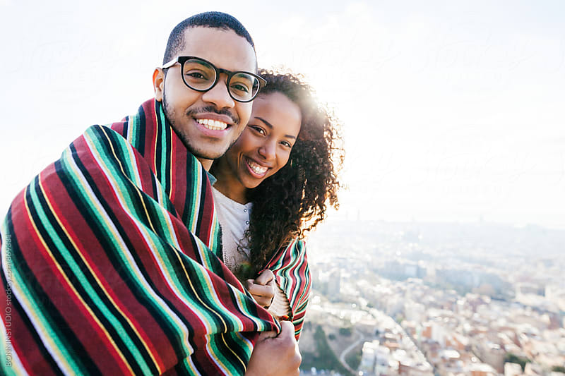 Portrait of couple covering with blanket above city. by BONNINSTUDIO for Stocksy United