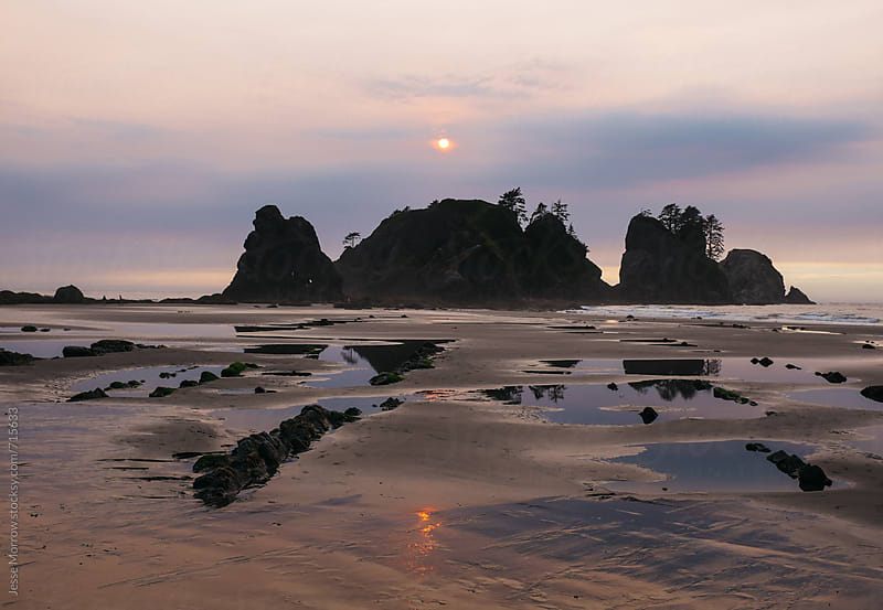 sun setting behind arches at shi shi beach washington by Jesse Morrow for Stocksy United