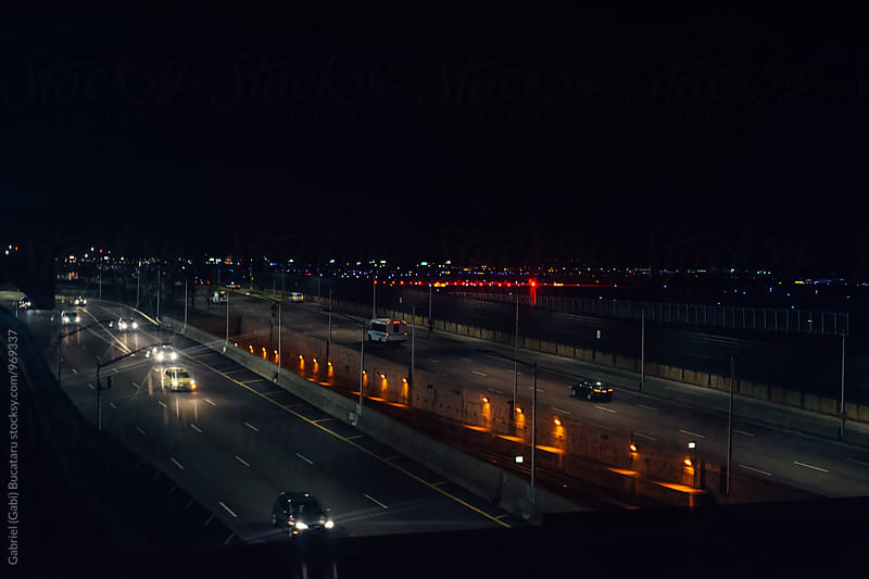 Cars on a highway at night from an airplane window by Gabriel (Gabi) Bucataru for Stocksy United