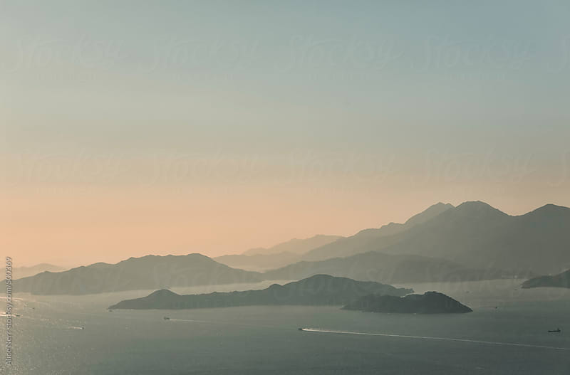 Mysterious foggy islands in soft pinkish-blue sunset light by Alice Nerr for Stocksy United