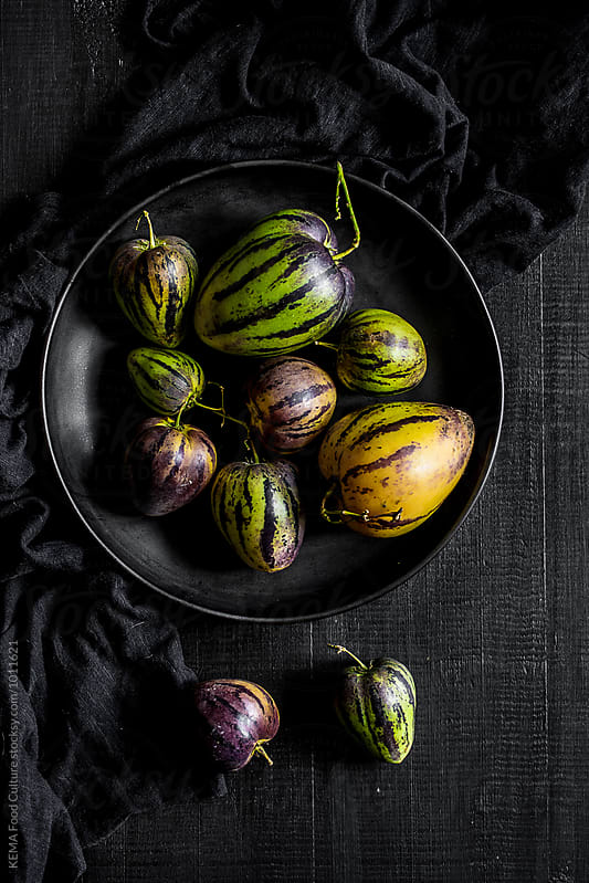 Pear-melons on a black wooden table by KEMA Food Culture for Stocksy United