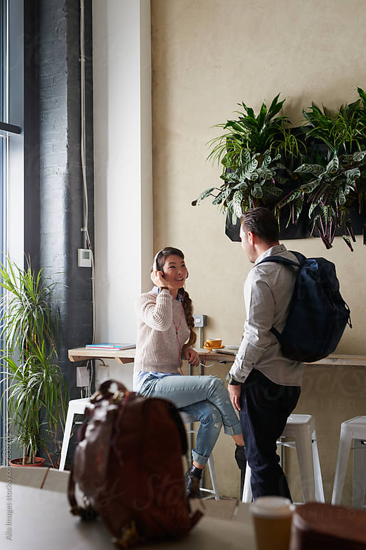 Young couple dressed smart casual surrounded by travel bags and coffee relaxing in cafe by Aila Images for Stocksy United