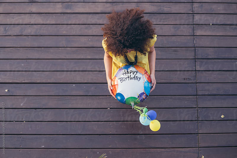 Birds eye view of a curly haired woman holding a Happy Birthday balloon by Jovo Jovanovic for Stocksy United