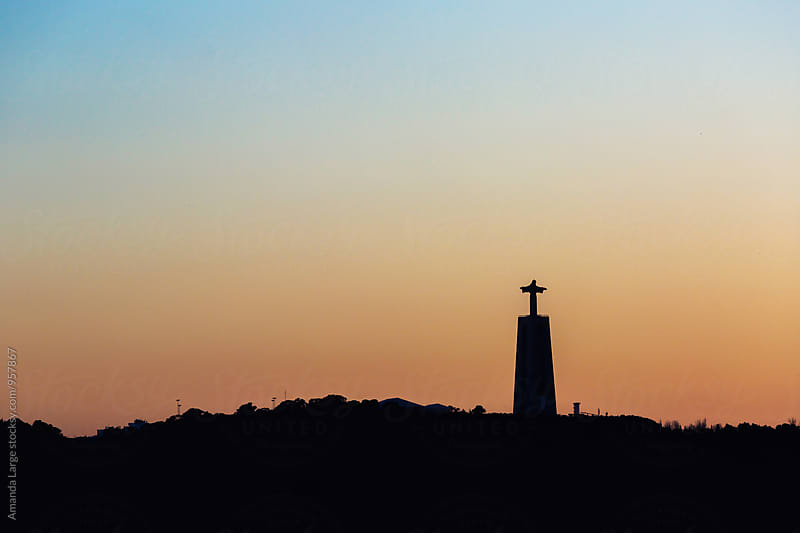 silhouette  at sunset of Cristo Rei monument in Lisbon, Portugal by Amanda Large for Stocksy United