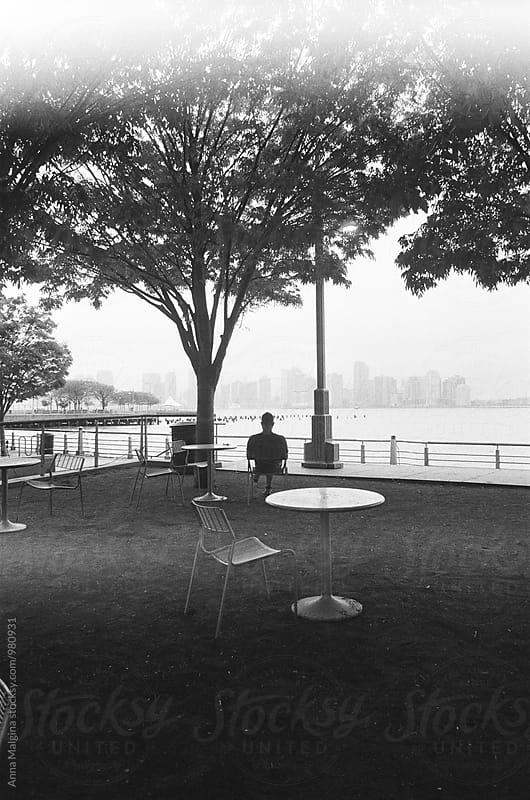 The black and white film photo of silhouette of man sitting nearby Hudson river by Anna Malgina for Stocksy United