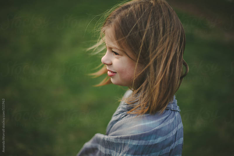 Profile portrait of young girl with sweet smile on a windy day by Amanda Worrall for Stocksy United