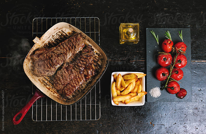 Steak,Chips and roasted vine tomato. by Darren Muir for Stocksy United