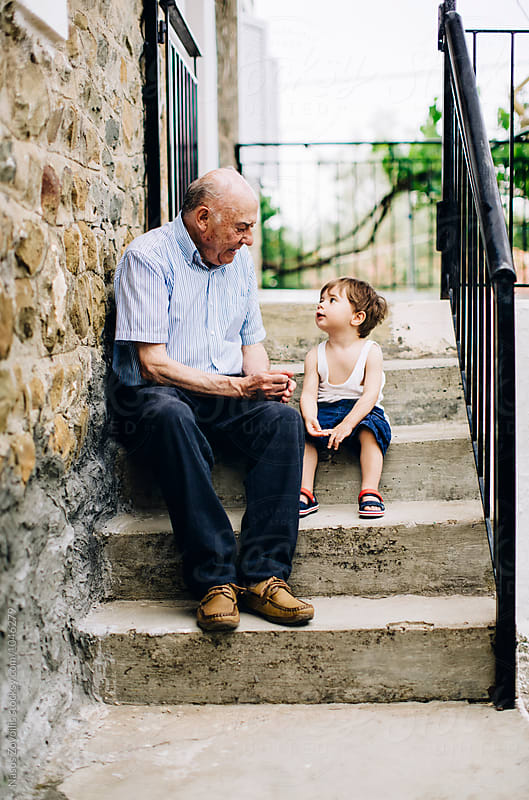 Grandfather talking to his grandson outdoor by Nasos Zovoilis for Stocksy United