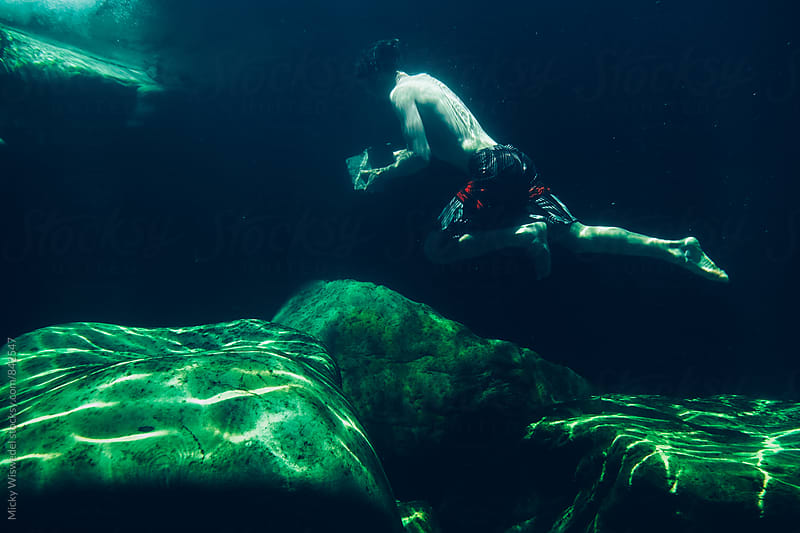 Man running underwater with a large rock in a mountain stream rock pool by Micky Wiswedel for Stocksy United