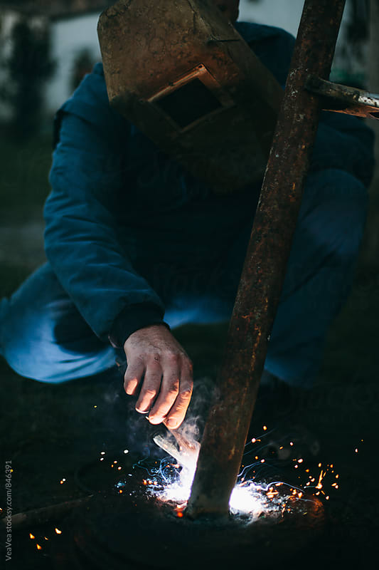 Welder welding outdoors by Marija Mandic for Stocksy United