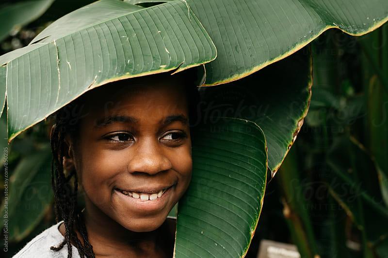 Black girl hiding in banana plant leaves by Gabriel (Gabi) Bucataru for Stocksy United