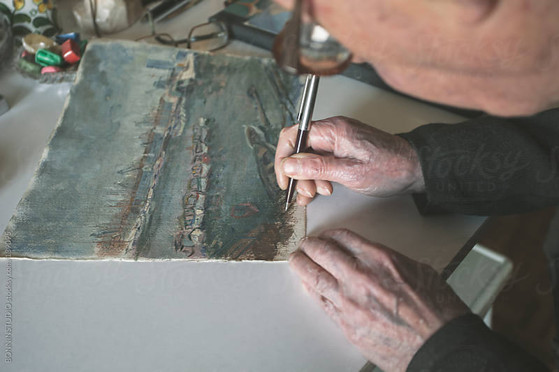 Old man signing his artistic pictures on desk. by BONNINSTUDIO for Stocksy United