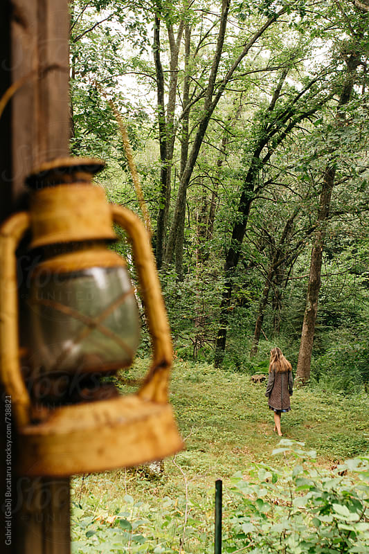 Woman walking in forest with lantern in foreground by Gabriel (Gabi) Bucataru for Stocksy United