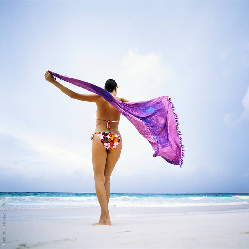 Woman on beach with sarong. by Hugh Sitton for Stocksy United