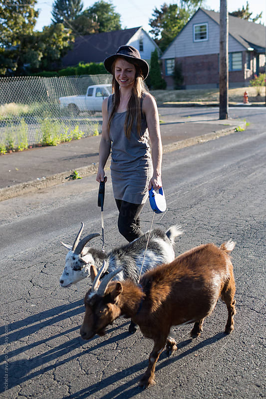 Woman walking with her little goats at sunset by michela ravasio for Stocksy United