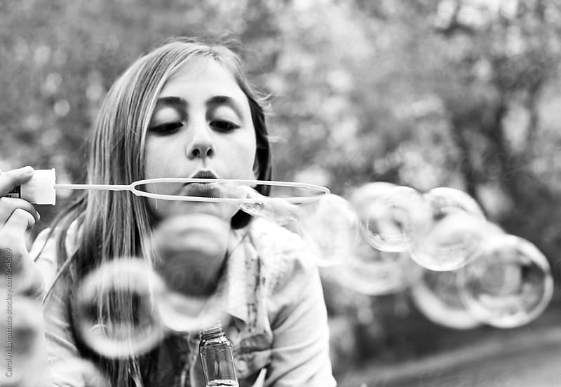 Black and white of a girl blowing big bubbles by Carolyn Lagattuta for Stocksy United
