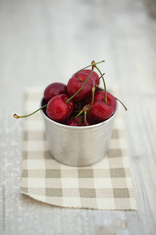 Handful of fresh red cherries in little old steel can on checked cloth by Laura Stolfi for Stocksy United