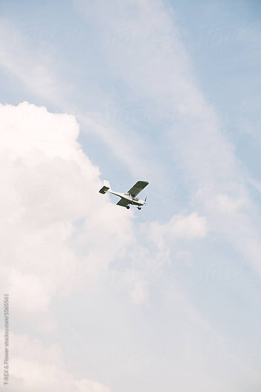 Plane crossing blue sky with white clouds by Danil Nevsky for Stocksy United
