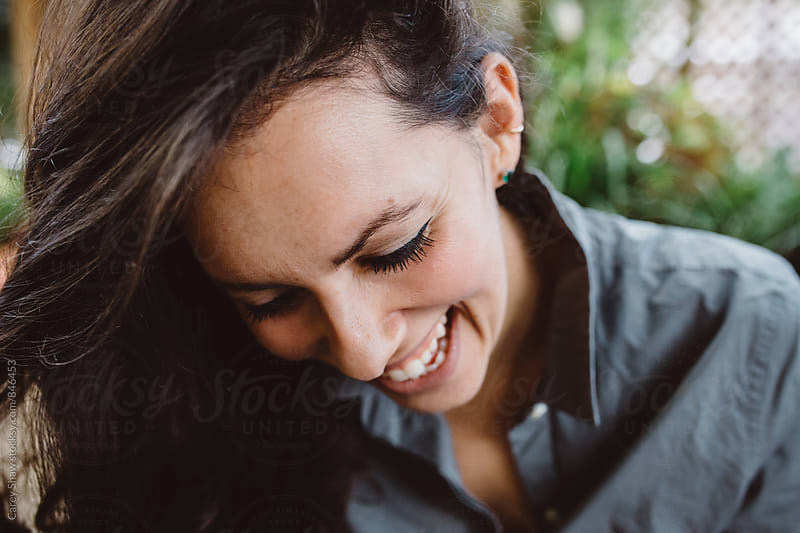 Attractive smiling woman looking down by Carey Shaw for Stocksy United