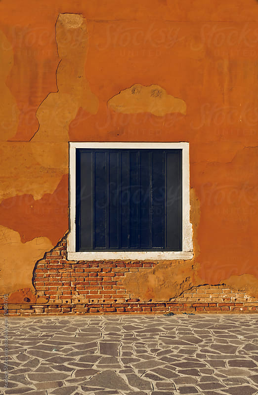 Mediterranean house detail/blue square window/opening on rustic orange wall.Venice/Italy by Audrey Shtecinjo for Stocksy United