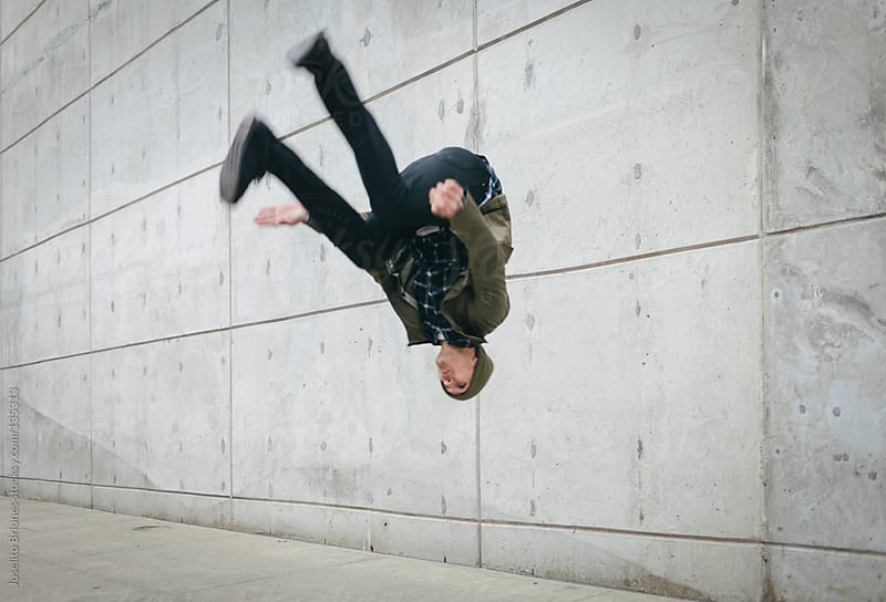 Young Man Doing a Backflip against Concrete Background by Joselito Briones for Stocksy United