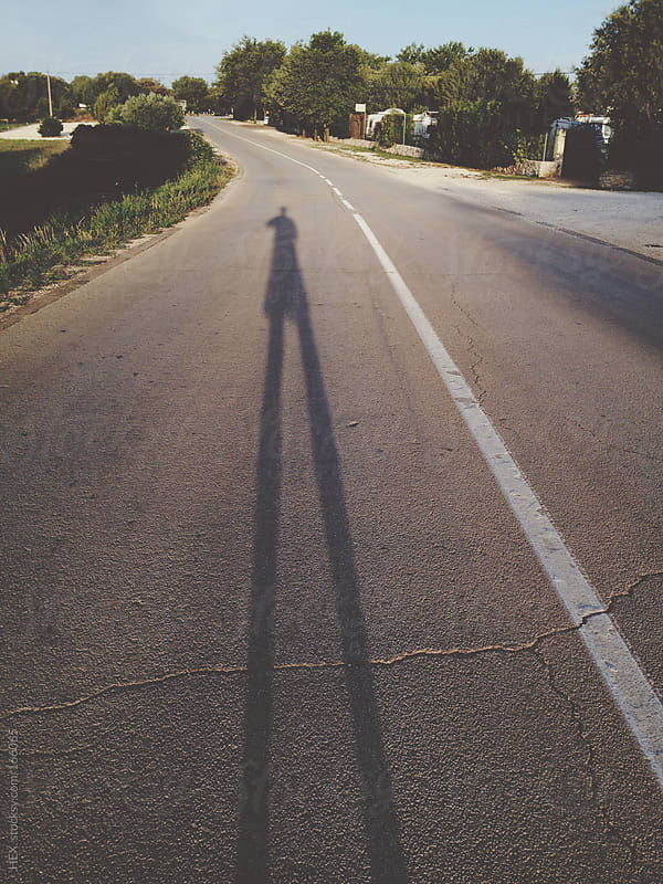 Man Casts Long Shadow on the Street by HEX. for Stocksy United