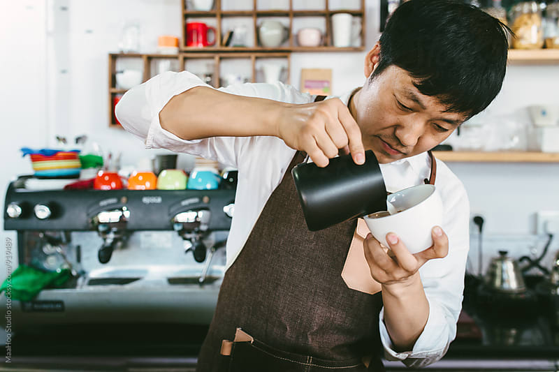 Young coffee shop owner making latte by MaaHoo Studio for Stocksy United