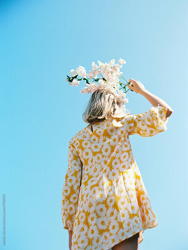 blonde girl with yellow floral dress against blue sky with flowers on her head by wendy laurel for Stocksy United