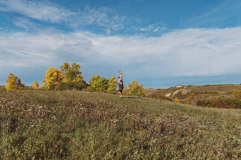 Father and daughter walking on hill by Carey Shaw for Stocksy United