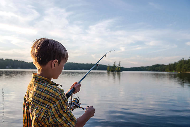 Boy on a lake reels in the line on his fishing rod by Cara Slifka for Stocksy United