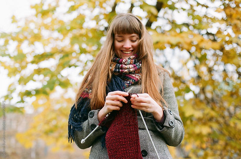Happy young woman knitting outdoors by Liubov Burakova for Stocksy United