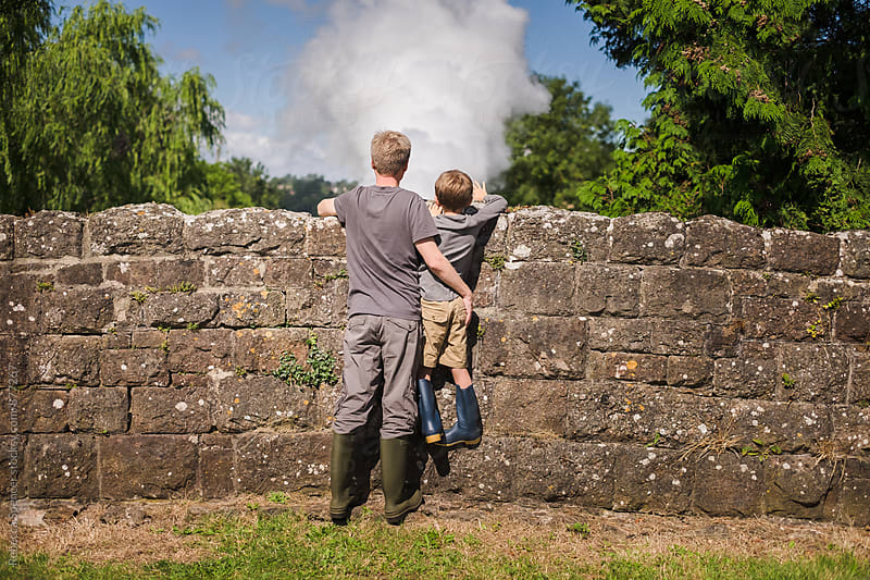 Child and Dad watch steam train from bridge by Rebecca Spencer for Stocksy United