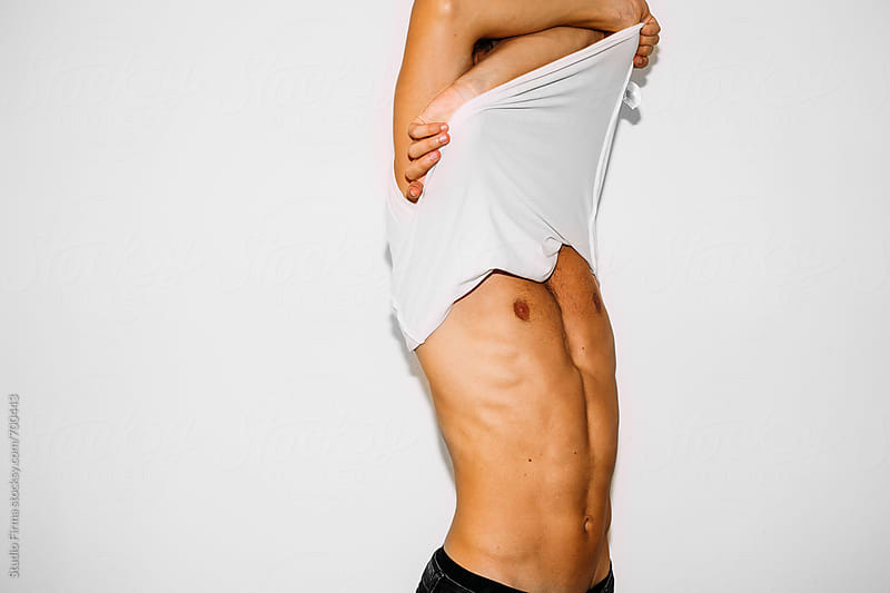 Smiling Young Man Removing T Shirt . by Studio Firma for Stocksy United