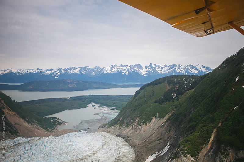 Flying over craggy peeks and glaciers in Alaska  by Shelly Perry for Stocksy United