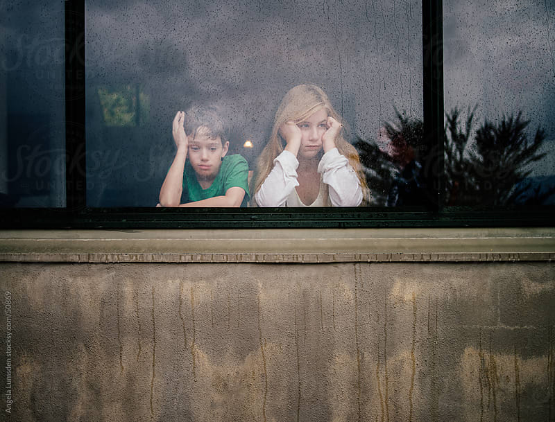Children looking out a window on a rainy day by Angela Lumsden for Stocksy United