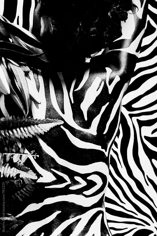 Zebra stripes on woman's back standing in front of a striped background by Beatrix Boros for Stocksy United