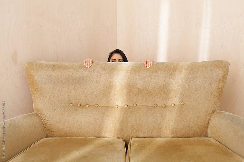 young woman hiding behind a retro couch by Ulaş and Merve for Stocksy United