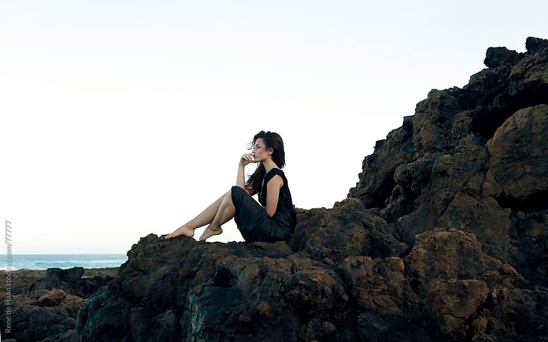 girl sitting on rock, waiting by Rene de Haan for Stocksy United