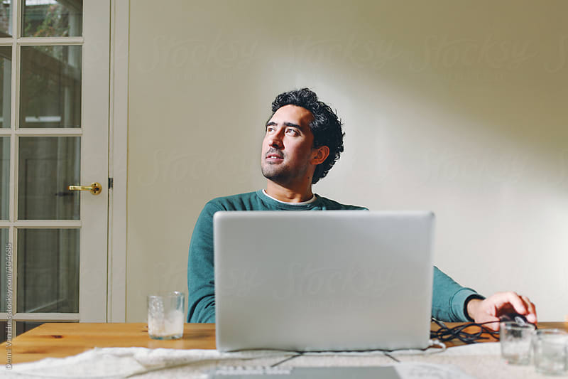 Man working at home on a laptop  by Denni Van Huis for Stocksy United