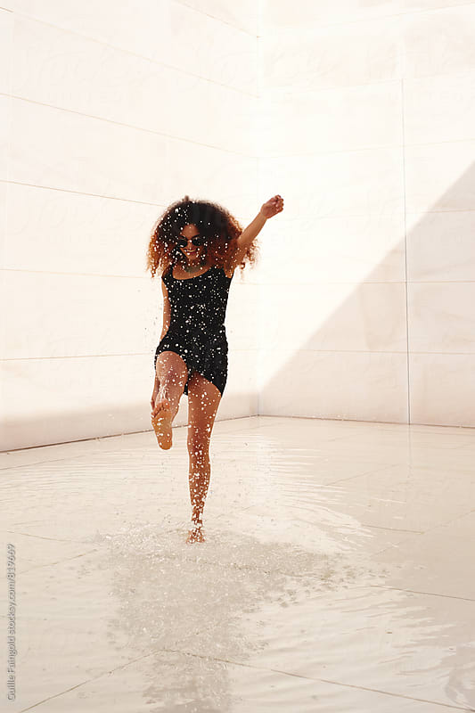 Young mulatto woman dancing in pool with bare feet by Guille Faingold for Stocksy United