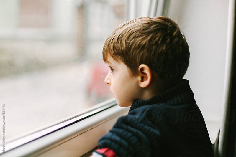 Boy looking through the window - horizontal by Marija Kovac for Stocksy United