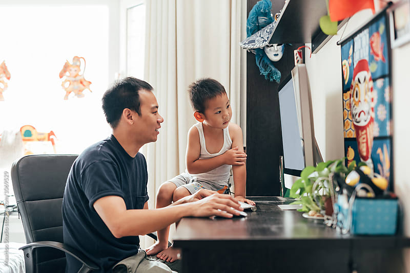 Father and son using computer at home by MaaHoo Studio for Stocksy United