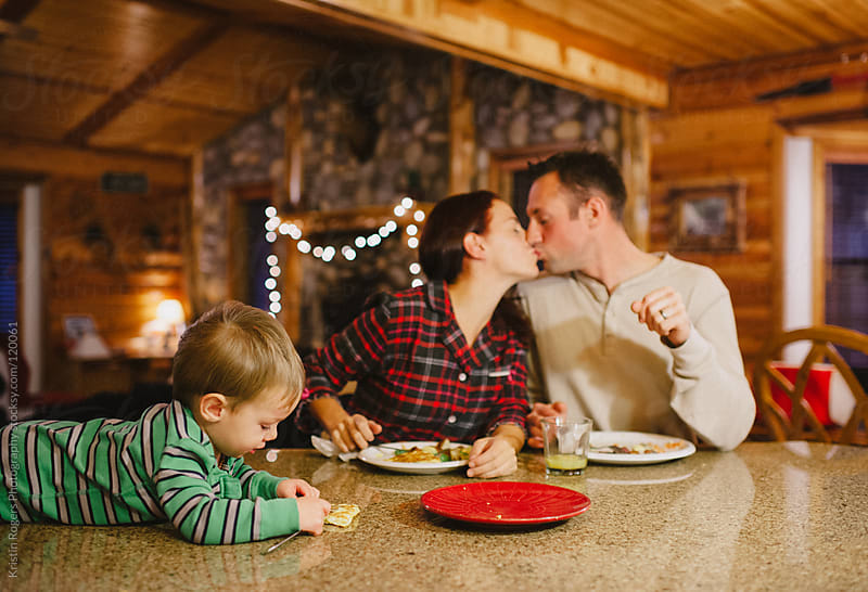 Parents kiss while baby plays during meal by Kristin Rogers Photography for Stocksy United