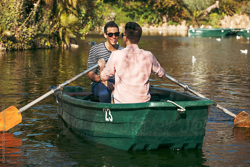Smiling gay couple relaxing on boat at lake. by BONNINSTUDIO for Stocksy United