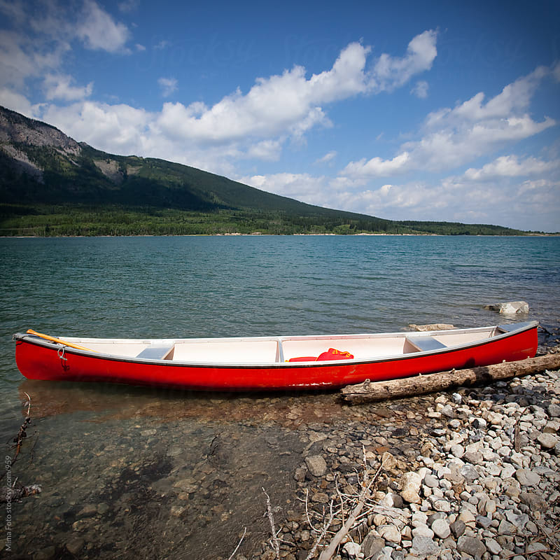 Red boat on a mountain lake in Alberta by Mima Foto for Stocksy United