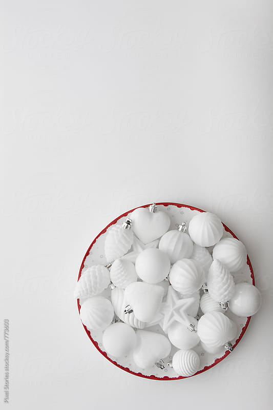 White Christmas baubles in dish on white background by Pixel Stories for Stocksy United