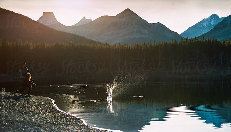 A couple skipping stones into a mountain pond. by Riley J.B. for Stocksy United